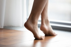 Crop close up of young woman barefoot step on warm wooden floor in bedroom or living room, female feet legs walk in room with underfloor electric heating at modern home or house