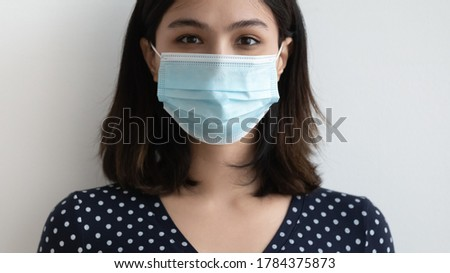 Crop close up portrait of young Asian woman in medical face mask isolated in grey studio background, millennial Vietnamese girl wear protective facial cover against covid-19, corona virus concept