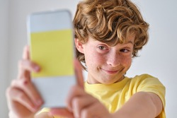 Crop cunning child with brown hair taking self portrait on mobile phone on light background