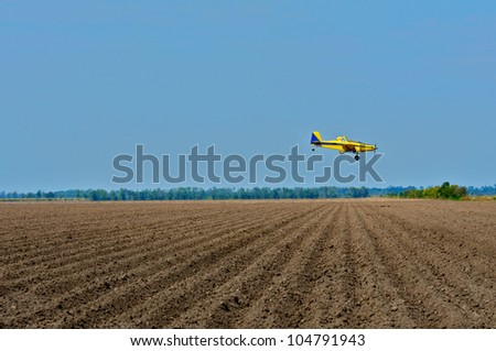 Crop duster approaching fields.