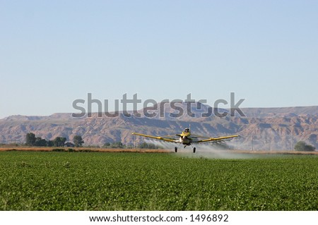 Crop duster dusting field in Wyoming valley