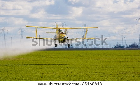 crop duster spraying insecticide on crops in central California - stock photo