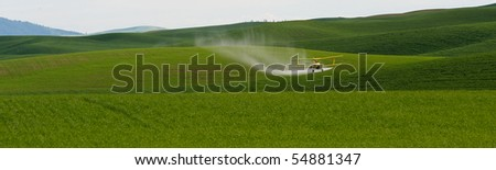 Crop dusting airplane applying Pesticide to the wheat fields of the Palouse