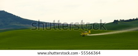 Crop dusting airplane spraying pesticide on wheat fields in the Palousezfz