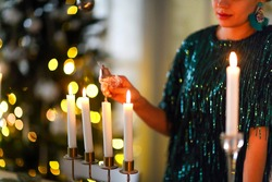 Crop female in fancy shiny dress and putting out candle flame with snuffer bell after celebrating Christmas holiday at home with fir tree