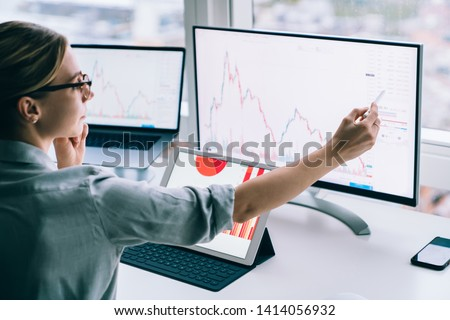 Crop formal businesswoman pointing at statistical chart on display of computer working at table with gadgets in modern office near window