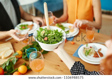 Crop hand passing green salad in white bowl while friends eating together
