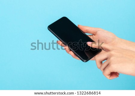 Crop hands of woman tapping on touchscreen of smartphone on blue background  #1322686814