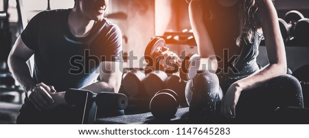Crop image of beautiful sport girl with dumbbell in hand with personal trainer in professional gym, color filter effect selective focus. #1147645283