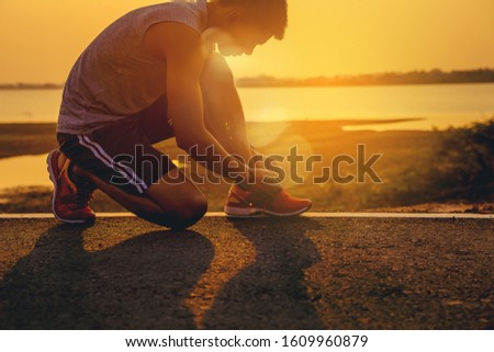 Crop image of man runner lace his shoes and prepare to jogging with sunset background