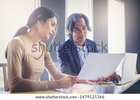 Crop image of young attractive businesswoman working with paperwork has been guided and consulting by senior colleague