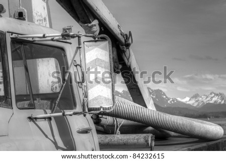 Crop of an old work truck in Alaska with mountains in the background, black and white.