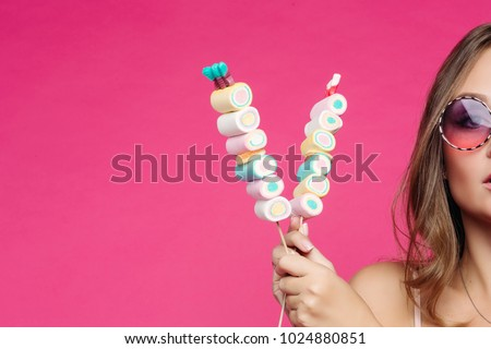 Crop of beautiful and seductive girl wearing in pink sunglasses with makeup like doll, posing at studio with marshmallow candy on stick. Pretty woman in violet sunglasses holding candies. Fashion.