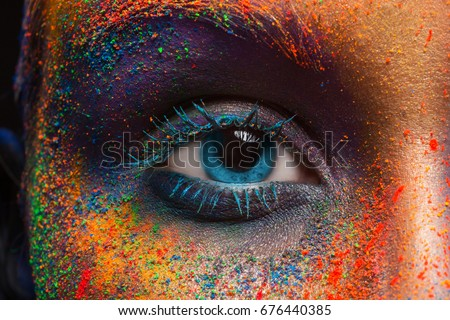 Crop of female eye with colorful make up. Beautiful fashion model with creative art makeup. Abstract colourful splash make-up. Holi festival #676440385
