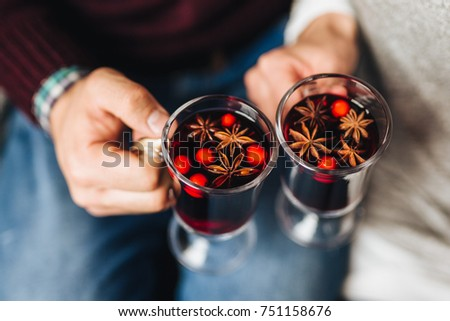 Crop people clinking with glasses full of mulled wine withs spices.  Сток-фото ©