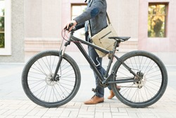 Crop photo of an active businessman carrying a messenger bag and walking his bike to the office. Man using an eco-friendly vehicle to commute to work