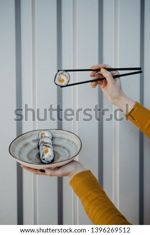 Crop picture girl eating sushi