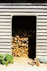 Crop picture of the storage filled with pile of firewood or fuelwood from countryside of Australia. The storage or firewood shed made from wood, a small bush plant at the front.