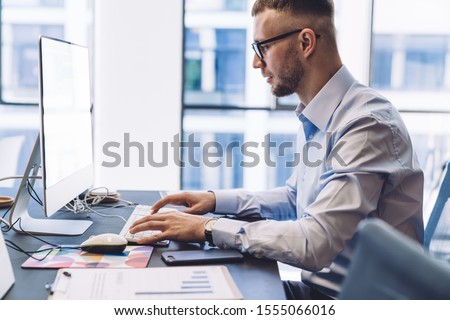 Crop side view of adult male worker in formal shirt and glasses sitting at desk with documents and working on person computer with empty white screen in workplace