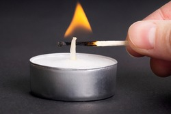 Crop view of a female hand lighting a tea candle with a burning match against a grey background.