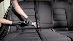 Crop view of hands in black gloves using vacuum cleaner on passenger seat in car