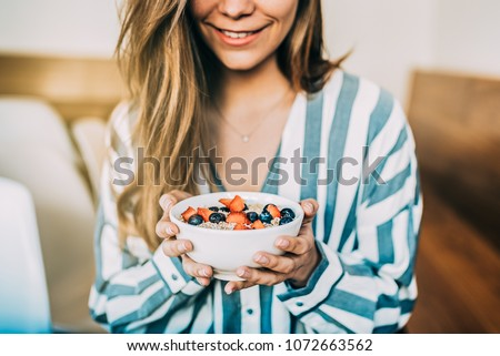 Crop woman close up eating oat and fruits bowl for breakfast #1072663562
