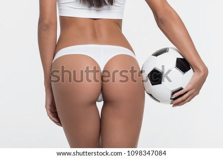 Crop woman in lingerie holding soccer ball