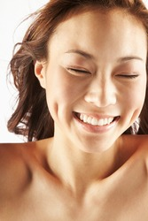 Crop young happy Asian female with perfect skin and dimples smiling with closed eyes against white background
