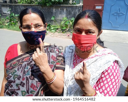 Cropped and partial view of Two Indian women wearing virus protection masks, outside, after giving vote on West Bengal Legislative Assembly election, India, 2021. Сток-фото ©