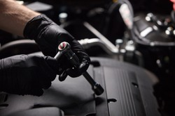 cropped auto mechanic male use wrench and other tools for fixing a car engine, working alone. close-up