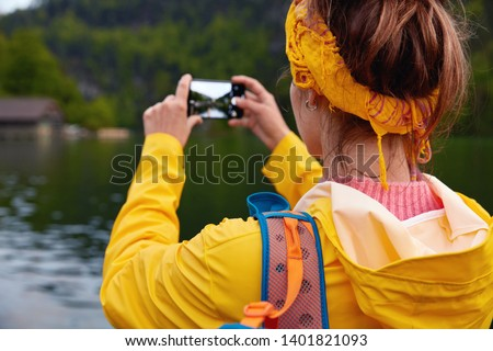 Cropped back view image of female wanderer in yellow raincoat, makes photo of beautiful lake near green forest, takes pics for remembering about wonderful trip and sharing in social networks