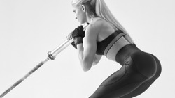 Cropped black and white photo of confident young woman exercising with barbell at fitness gym Female bodybuilder turned back working out with heavy weights at training gym