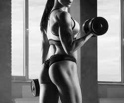Cropped black and white photo of strong fit model training in gym , doing fitness exercises with heavy dumbbells. Having athletic muscles, healthy body and tanned skin. Looking strong, feeling good.