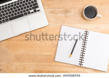 cropped bronze notebook computer with black keyboard white letters matte black sharpened wooden pencil on blank recycle paper notebook and hot black coffee on light brown jointed rubberwood desktop #444408496