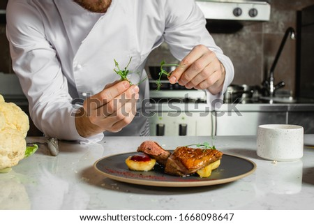 cropped caucasian chef-cook finishing delicious dish in the kitchen of restaurant. expert in culinary. food concept Stock photo ©