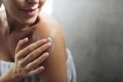 Cropped Caucasian woman putting body lotion on her shoulder.