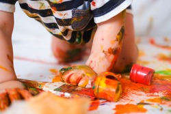 Cropped cheerful grimy baby crawls on the floor playing with paint. dirty kid close up. Happy leasure and play at home.