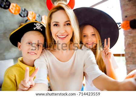 Cropped close up family portrait of three at halloween party. Happy blonde mommy and her cheerful kids - blond small witch and pirate, bonding, lady is making selfie, siblings showing like signs