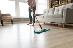 Cropped close up image of barefoot young woman in casual clothes washing heated wooden laminate warm floor using microfiber wet mop pad, doing homework cleaning routine, housekeeping job concept