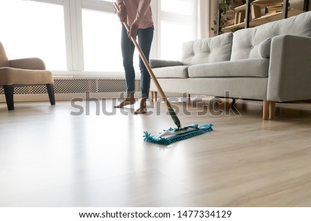 Cropped close up image of barefoot young woman in casual clothes washing heated wooden laminate warm floor using microfiber wet mop pad, doing homework cleaning routine, housekeeping job concept Stock foto ©