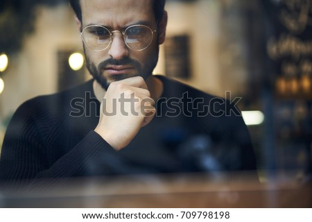 Cropped close up image of pensive bearded entrepreneur in optical spectacles for better views dressed in black sweatshirt.Pondering businessman in trendy eyeglasses thinking on blurred background #709798198