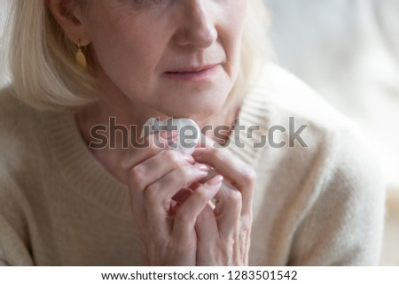 Cropped close up image of unhappy unhealthy middle aged blond woman crying holding in hands handkerchief, mature mature caucasian female sixty years feeling badly she puzzled with piled up problems