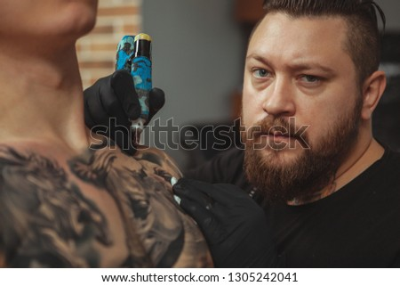 Cropped close up of a professional tattoo artist looking to the camera fiercely while working. Experienced tattooist tattooing chest of a male client. Professionalism, creativity concept