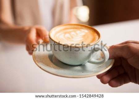Cropped close up of a woman taking cup of delicious coffee from barista. Professional barista handing coffee cup to female customer