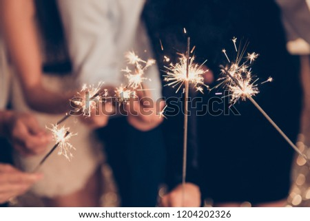 Cropped close-up photo of bengal fire sticks, sparkling, burning, elegant classy ladies and gentlemen's hands holding fire-sticks together, meeting, team, greetings, congrats, merry x-mas