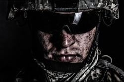 Cropped close up portrait of US special operations forces soldier, marine raider, modern combatant in helmet and glasses with dirty face after difficult military mission or battle looking at camera