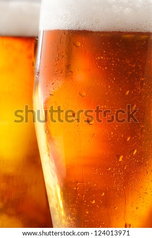 Cropped closeup of a glass of cold beer with a frothy head and water droplets from condensation beading the outside of the glass
