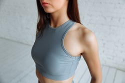 cropped closeup of the body of a fit woman wearing a sports bra, showing slim belly and press in diet fitness and concepts of healthy lifestyle, isolated on white brick background