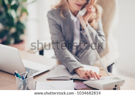 Cropped closeup photo of clever smart professional polite secretary in grey formal suit is calling to her boss, she is sitting at the table in office