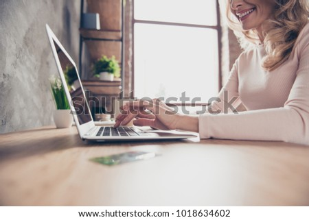 Cropped closeup photo of elegant woman's hands typing and searching information on the internet using her netbook